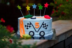 Birthday cake with mastic stars and cars figures for boy. five years old anniversary