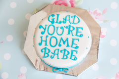 Birthday Cake with mastic text. Glad You're Home Babe on floral background Stock Images