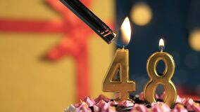 Free Birthday Cake Number 48 Golden Candles Burning By Lighter, Background Gift Yellow Box Tied Up With Red Ribbon. Close-up Royalty Free Stock Images - 172380629