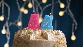 Birthday cake with 44 number burning by lighter pink candle on blue backgraund. Candles are set on fire. Slow motion