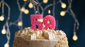 Birthday cake with 59 number burning by lighter pink candle on blue backgraund. Candles are set on fire. Slow motion
