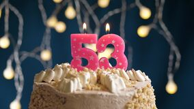 Birthday cake with 53 number burning by lighter pink candle on blue backgraund. Candles are set on fire. Slow motion