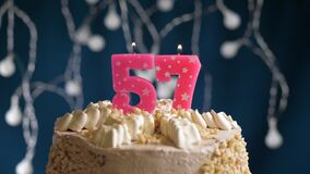 Birthday cake with 57 number burning by lighter pink candle on blue backgraund. Candles are set on fire. Slow motion