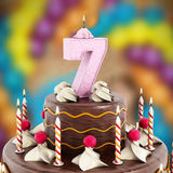 Birthday cake with number 7 lit candle Stock Photo