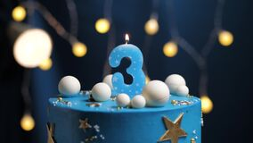 Birthday cake number 3 stars sky and moon concept, blue candle is fire by lighter and then blows out. Copy space on