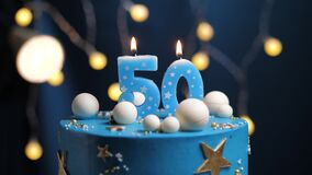 Birthday cake number 50 stars sky and moon concept, blue candle is fire by lighter and then blows out. Copy space on