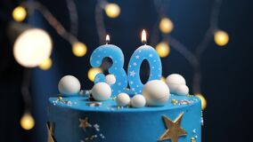 Birthday cake number 30 stars sky and moon concept, blue candle is fire by lighter and then blows out. Copy space on