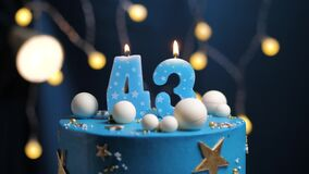 Birthday cake number 43 stars sky and moon concept, blue candle is fire by lighter and then blows out. Copy space on