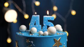 Birthday cake number 45 stars sky and moon concept, blue candle is fire by lighter and then blows out. Copy space on