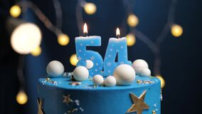 Birthday cake number 54 stars sky and moon concept, blue candle is fire by lighter and then blows out. Copy space on