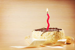 Birthday cake with one decorative burning candle Stock Photos
