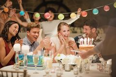 Birthday Cake At A Party. Birthday cake being brought out to a small group of people at a birthday party Stock Image