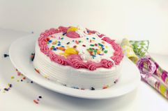 Birthday Cake and Party Blowers Royalty Free Stock Image