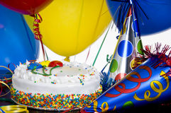 Birthday Cake, party hats and balloons Royalty Free Stock Photos
