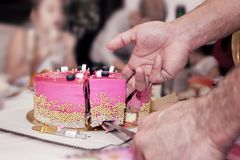 Birthday cake pink high shiny adorned with shiny beads cut into pieces of men`s hands. Birthday Cake decorated with pink shiny high polished beads cut into Stock Images