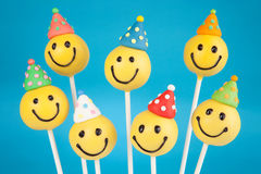 Birthday cake pops. Smiley face cake pops . Round-shaped mini cakes on sticks royalty free stock images