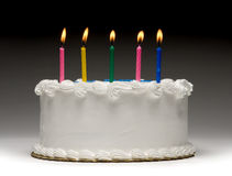 Birthday Cake Profile. White birthday cake profile on graident background with five colorful lit candles Stock Photos