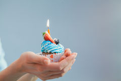 Birthday cake single candle in hands over blue background. Holid. Birthday cupcake with single candle in female hands over blue background. Holiday concept Royalty Free Stock Photos