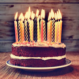 Birthday cake with some lit candles, filtered. A cake topped with some lit candles before blowing out the cake, on a rustic wooden table, with a filtered effect Royalty Free Stock Images