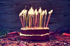 Birthday cake with some lit candles, filtered. A cake topped with some lit candles before blowing out the cake, on a rustic wooden table full of confetti, party Royalty Free Stock Image