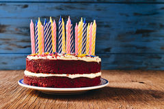Birthday cake with some unlit candles. A red velvet cake topped with some unlit candles on a rustic wooden table Royalty Free Stock Image