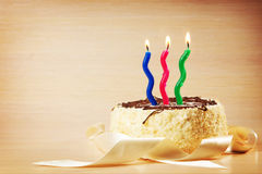 Birthday cake with three decorative burning candles. Against beige background Stock Photography
