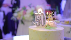 Birthday cake with the 50 year and two candles. Applause on the background of the cake.