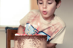Birthday cake. Young boy blowing candles on his birthday cake stock photo