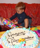 Birthday Cake with young kid opening a present in background Royalty Free Stock Photo