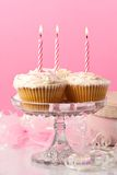 Birthday Cakes. Birthday cupcakes with red striped lit candles with present and streamers in background Royalty Free Stock Photo