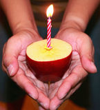 Birthday candle. And apple in hand Royalty Free Stock Images