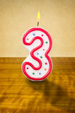 Birthday candle number 3. Burning birthday candle number 3 Royalty Free Stock Images