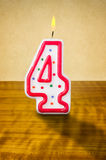Birthday candle number 4. Burning birthday candle number 4 Royalty Free Stock Images