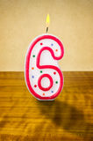 Birthday candle number 6. Burning birthday candle number 6 Royalty Free Stock Images