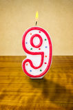 Birthday candle number 9. Burning birthday candle number 9 Royalty Free Stock Photo