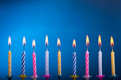 Birthday candles. Birthday colour candles with fire on blue background Stock Image