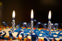 Birthday Candles. On cake against dark background Royalty Free Stock Photos