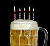 Birthday candles in beer. Striped birthday candles in a mug of beer stock photography