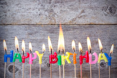 Birthday candles burn against wooden background Royalty Free Stock Photo