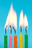 Birthday candles burn on blue background Stock Images