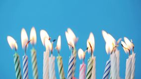 Birthday candles burning over blue background stock video footage