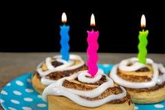 Birthday candles in cinnamon rolls Stock Photo