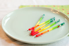 Birthday candles on plate. Rainbow birthday candles pulled from the cake and laid on a blue plate. Bits of frosting cling to the drippy, burned, candles. A green Stock Photo