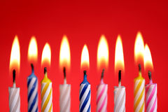 Birthday candles on red. Illuminated birthday candles on red background royalty free stock images