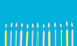Birthday candles in a row with flames Stock Photo