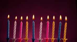 Birthday candles. Ten colorful illuminated birthday candles over purple background Stock Images