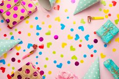 Birthday caps, blowers and confetti on a bright background.  stock photography