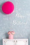 Birthday card. Postcard in pastel colors with words Happy Birthday. One big pink balloon and flower box.