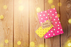 Birthday celebration concept with gift box and bokeh lights on wooden background. Royalty Free Stock Photography