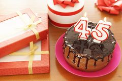 Birthday celebration at forty five years. A cake with burning candles in the form of numbers and a lot of gifts on a table royalty free stock photo